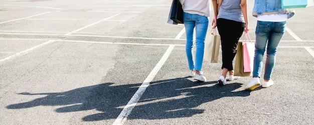 Belle ragazze asiatiche che tengono i sacchetti della spesa mentre stando all'aperto Foto Gratuite