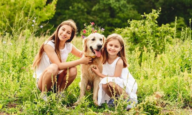 Belle ragazze che giocano con il cane carino Foto Premium
