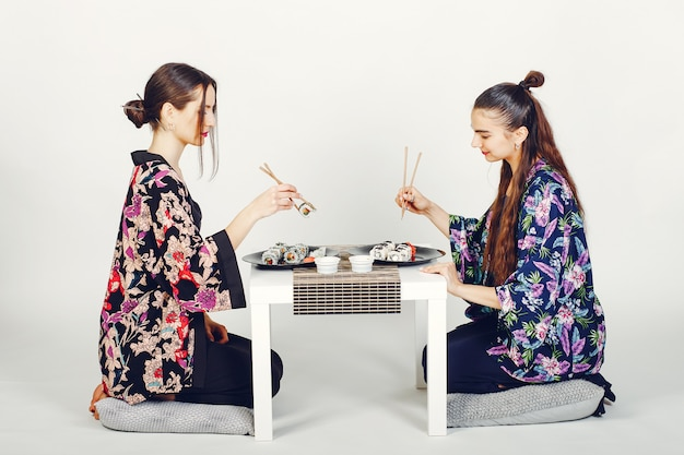 Belle ragazze che mangiano un sushi in uno studio Foto Gratuite