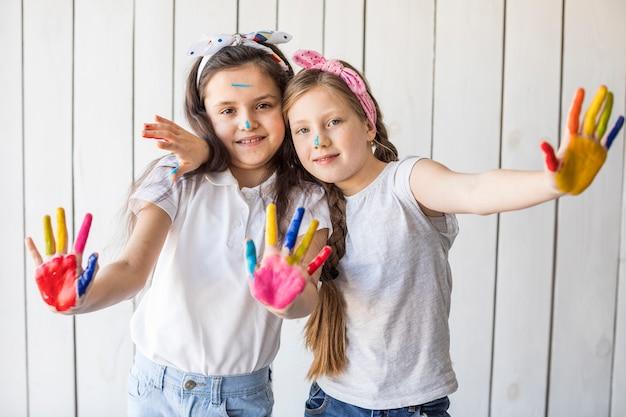Belle ragazze che mostrano le loro mani dipinte che stanno contro la parete di legno bianca Foto Gratuite