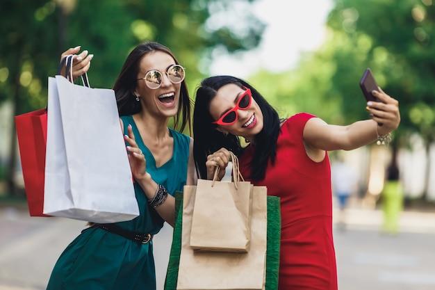 Belle ragazze felici in occhiali da sole che tengono i sacchetti della spesa, facendo selfie su smart phone e sorridente. Foto Premium