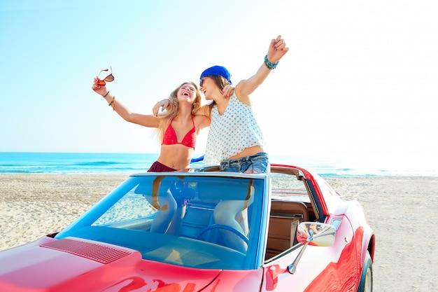 Belle ragazze festa ballando in una macchina sulla spiaggia Foto Premium