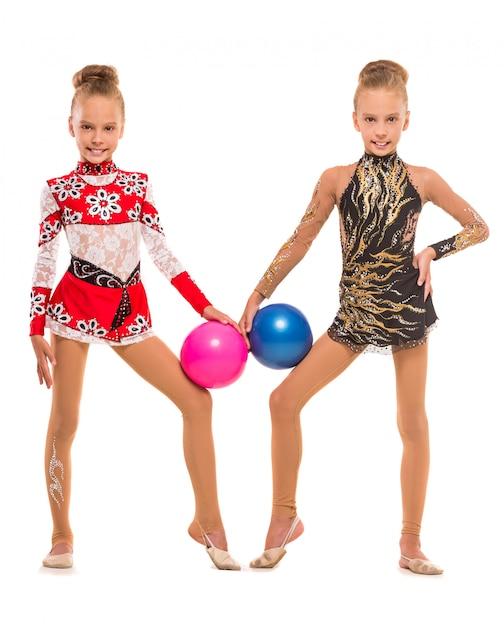 Belle ragazze gemelle sono in posa con le palle. Foto Premium