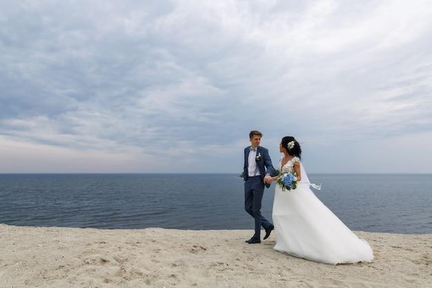 Belle sposi felici sposi al giorno delle nozze all'aperto in spiaggia Foto Premium