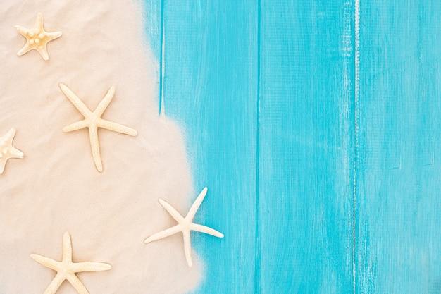 Belle stelle marine con la sabbia su fondo di legno blu Foto Gratuite