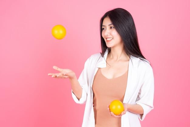 Bellezza donna asiatica ragazza carina sentire felice holdind arancione frutta per una buona salute su sfondo rosa Foto Gratuite