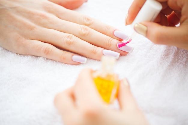 Bellezza e cura. manicure master che applica smalto nel salone di bellezza. mani di belle donne con un manicure perfetto. manicure spa Foto Premium