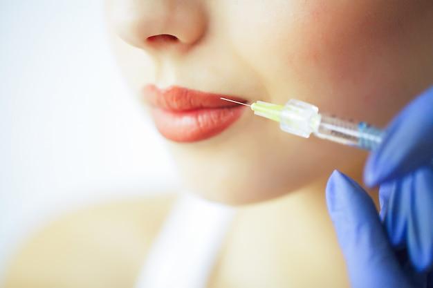 Bellezza e cura. ritratto di una giovane donna con un bel viso. un cosmetologo fa le iniezioni. alta risoluzione Foto Premium