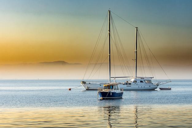 Bellezza sunrise sulla baia con yacht Foto Premium