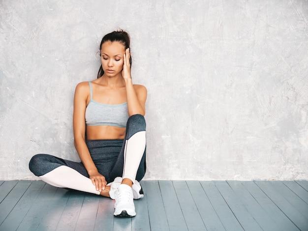 Bellissima modella con corpo abbronzato perfetto. donna seduta in studio vicino al muro grigio Foto Gratuite