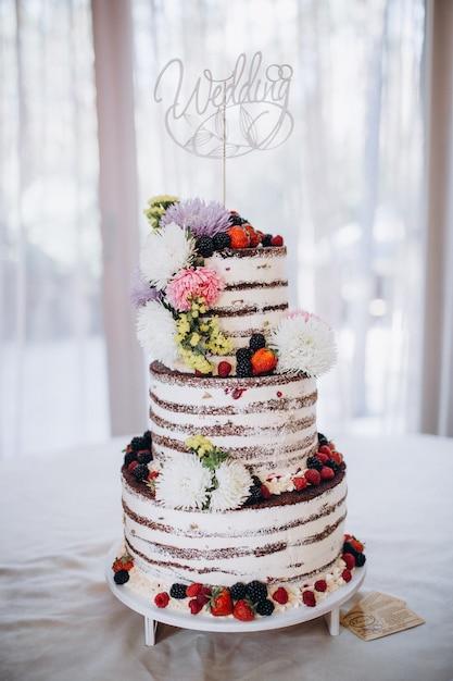 Bellissima torta nuziale rustica decorata con fiori Foto Premium