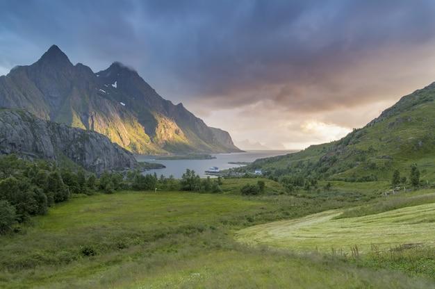 Bellissima valle coperta d'erba da un lago con una magnifica montagna Foto Gratuite