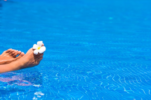 Bellissimi piedi femminili con pedicure e fiori tropicali in piscina Foto Premium