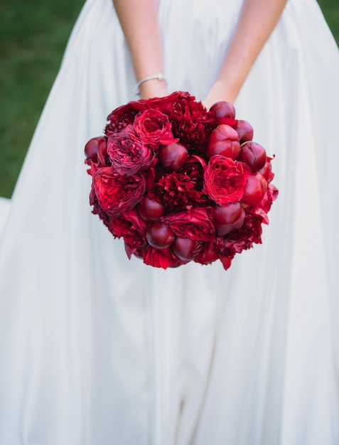 Bellissimo bouquet da sposa rosso fatto di peonie nelle mani della sposa Foto Gratuite