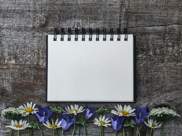 Bellissimo bouquet di fiori luminosi e blocco note Foto Premium