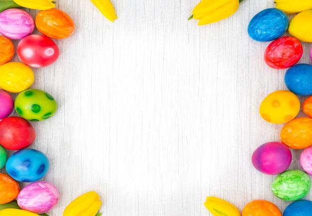 Bellissimo gruppo di uova di pasqua in primavera del giorno di pasqua, uova rosse, blu, viola e giallo con tulipani Foto Premium