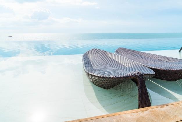 Bellissimo ombrellone e sedia di lusso intorno alla piscina all'aperto in hotel e resort Foto Premium