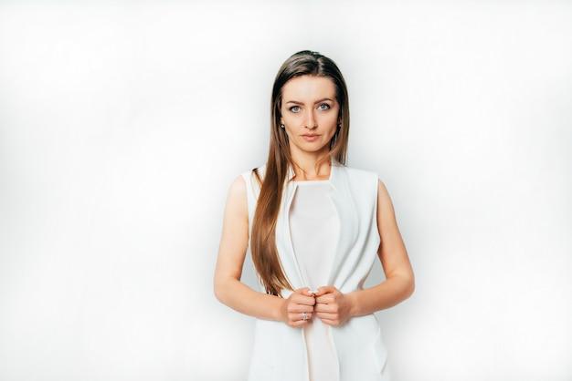 Bellissimo presentatore televisivo con i capelli lunghi si trova in un abito bianco in studio Foto Premium