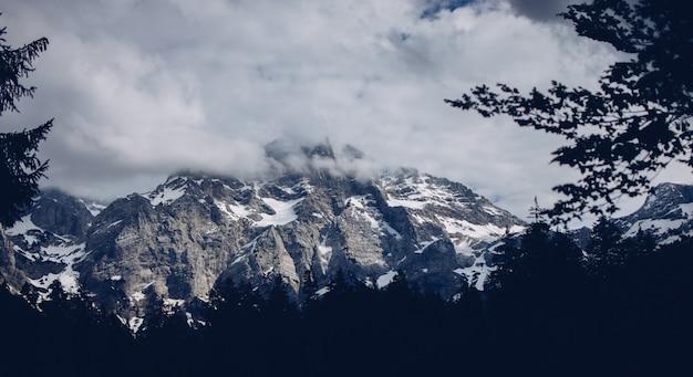 Bellissimo scatto di montagne rocciose e innevate con incredibili nuvole e vegetazione intorno Foto Gratuite