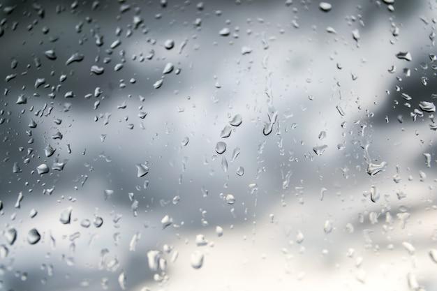 Bellissimo sfondo di natura di pioggia e goccia di rugiada sul vetro. Foto Premium