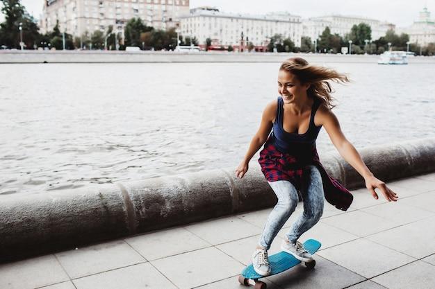 Bellissimo skateboard biondo sul lungomare Foto Gratuite