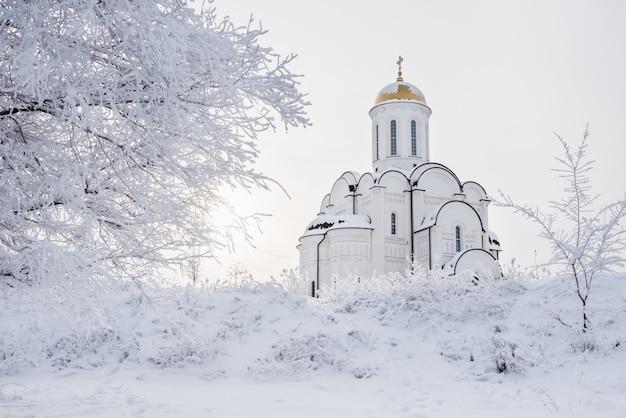 Bellissimo tempio bianco ortodosso tra alberi innevati Foto Premium