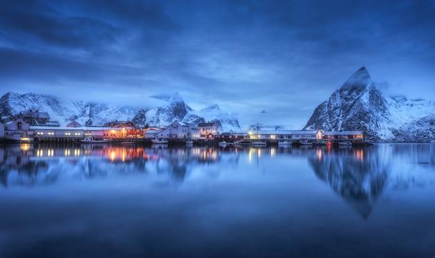 Bellissimo villaggio di pescatori con barche di notte Foto Premium