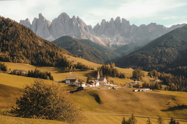 Bellissimo villaggio su una collina erbosa asciutta circondata dalle montagne boscose di giorno Foto Gratuite