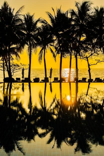 Bello albero del cocco della siluetta sul cielo intorno alla piscina nell'oceano vicino vicino del mare della località di soggiorno dell'hotel b Foto Gratuite