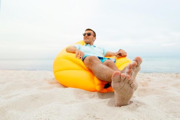 Bello allegro e godendo il tempo libero, sdraiato sul divano aria lamzac e ascoltando musica Foto Gratuite