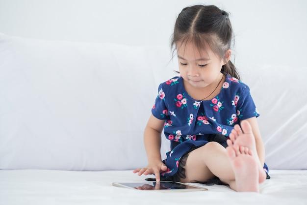 Bello bambino asiatico della ragazza che per mezzo del computer della compressa con lo spazio della copia Foto Premium