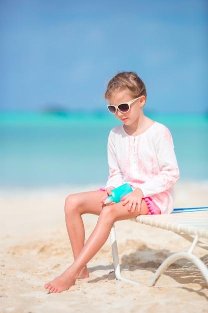 Bello bambino con la bottiglia di crema solare sulla spiaggia tropicale Foto Premium