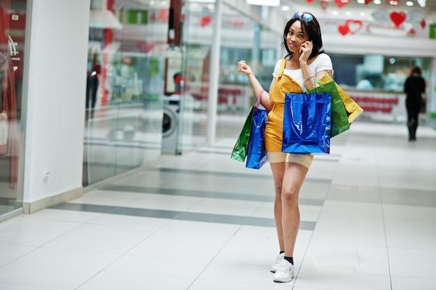 Bello cliente afroamericano ben vestito della donna con i sacchetti della spesa colorati, parlando sul telefono al centro commerciale. Foto Premium
