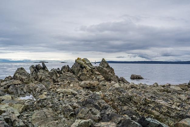 Bello colpo della scogliera rocciosa vicino al mare sotto un cielo Foto Gratuite