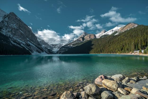 Bello colpo delle montagne che riflettono nel lago freddo sotto il cielo nuvoloso Foto Gratuite