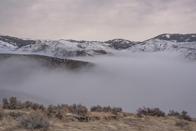 Bello colpo delle montagne nevose sopra la nebbia con un cielo nuvoloso Foto Gratuite
