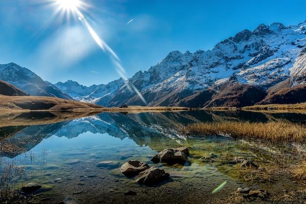 Bello colpo di un lago cristallino vicino ad una base di montagna nevosa durante il giorno soleggiato Foto Gratuite