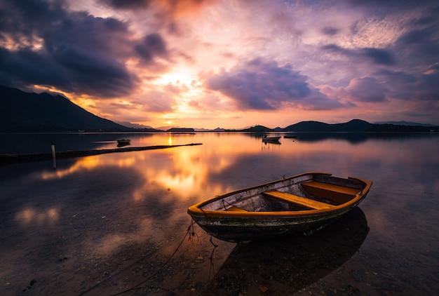Bello colpo di un piccolo lago con una barca a remi di legno a fuoco e incredibili nuvole nel cielo Foto Gratuite