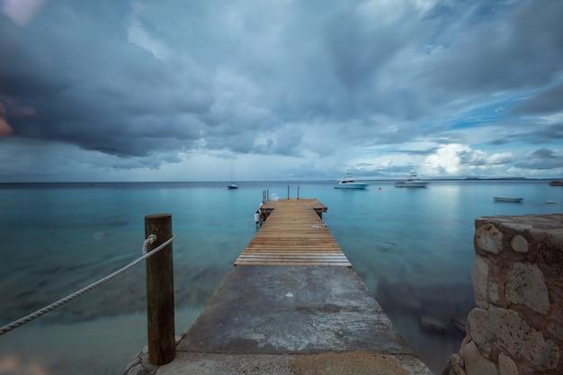 Bello colpo di un pilastro che conduce all'oceano sotto il cielo tenebroso nel bonaire, caraibico Foto Gratuite