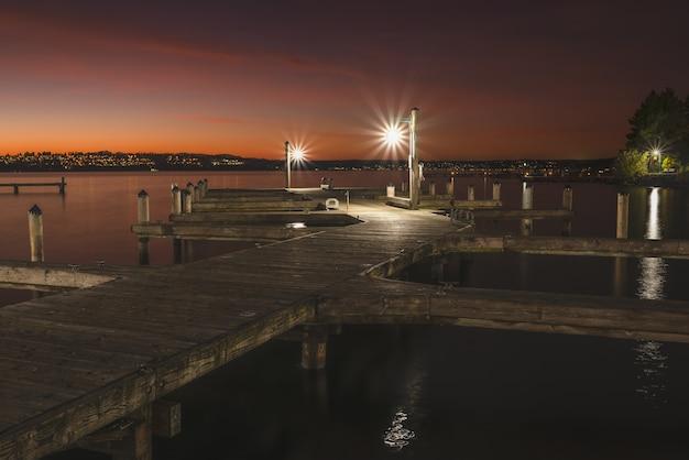Bello colpo di un pilastro di legno illuminato nel lago intorno alla città alla notte Foto Gratuite