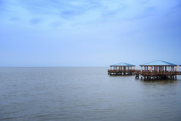 Bello colpo di un pilastro di legno sul mare sotto il cielo nuvoloso Foto Gratuite