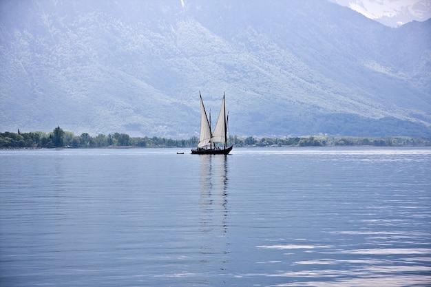 Bello colpo di una barca che naviga sull'acqua con le montagne boscose Foto Gratuite