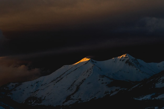 Bello colpo di una montagna coperta di neve durante la tarda notte Foto Gratuite