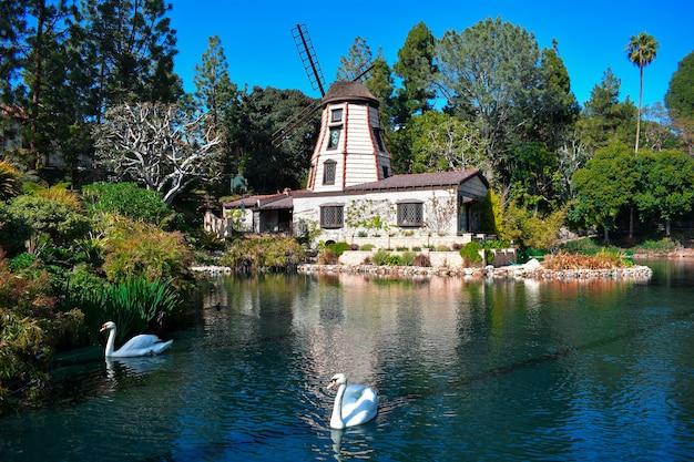 Bello colpo di una tenuta di campagna con un lago del cigno circondato da uno scenario verde Foto Gratuite