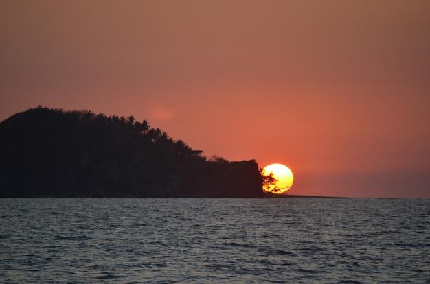 Bello colpo largo della siluetta di un isolotto coperto di alberi sopra dal mare sotto il cielo durante il tramonto Foto Gratuite