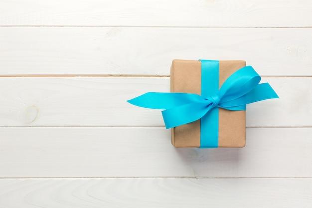 Bello contenitore di regalo con un arco blu sulla tavola di legno bianca, vista superiore Foto Premium