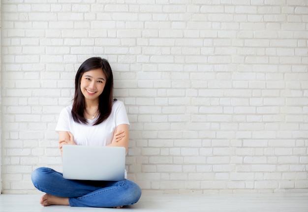 Bello della giovane donna asiatica del ritratto eccitato e felice di successo con il computer portatile Foto Premium