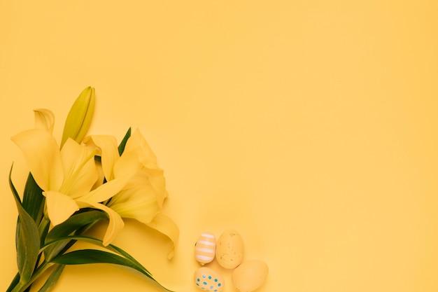 Bello fiore del giglio giallo con le uova di pasqua sul contesto giallo Foto Gratuite