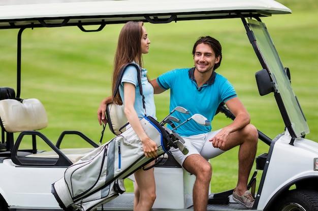 Bello giocatore di golf femminile che trasporta un sacchetto di golf Foto Gratuite