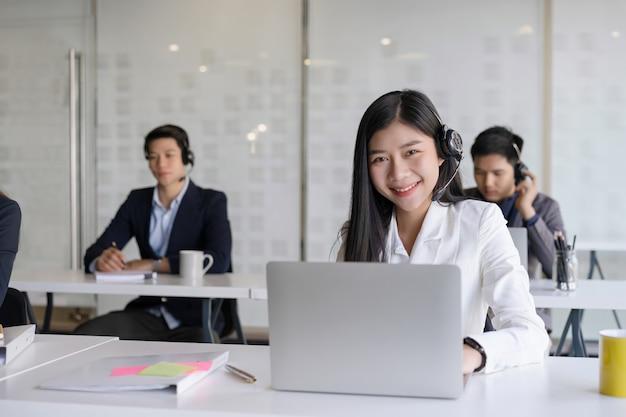 Bello giovane agente femminile di servizi di assistenza al cliente con la cuffia avricolare che funziona in un ufficio della call center. team di assistenza clienti supporto concetto di cura Foto Premium